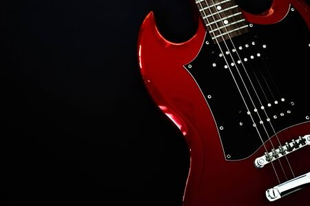 Red electric guitar closeup isolated on black background