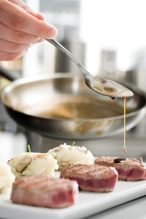 Chef add sause to a beef on professional kitchen Stock Photo