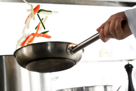 cooking chef: Chef hands with frying pan on professional kitchen