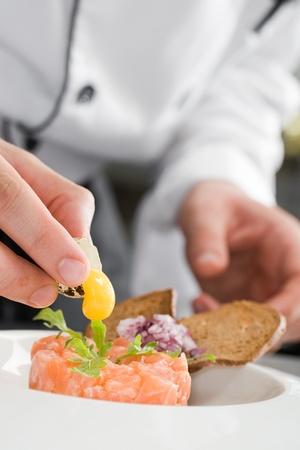 hombre cocinando: Ensalada chef prepearing salm�n Foto de archivo
