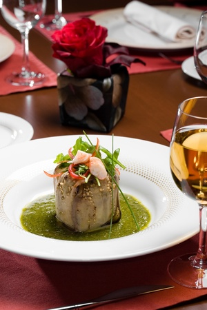 wine and dine: Baked eggplant, pepper,  shrimps salad in sauce on a table with a wine glass at restaurant