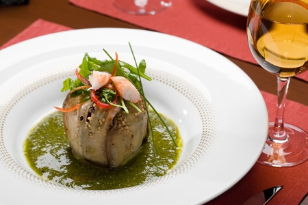 Baked eggplant, pepper,  shrimps salad in sauce on a table with a wine glass at restaurant