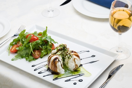 White salad in sauce on a table with a wine glass at restaurant photo