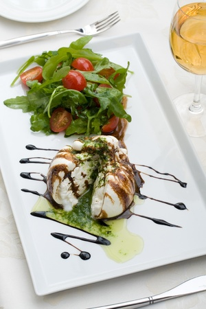 fine cuisine: White salad in sauce on a table with a wine glass at restaurant