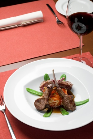 wine and dine: Rack of lamb on a table with a wine glass at restaurant Stock Photo