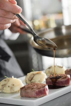 chef cocinando: Cocinero A�adir salsa a una vaca en la cocina profesional