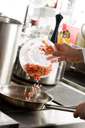 Chef hands add vegetables on frying pan on professional kitchen photo