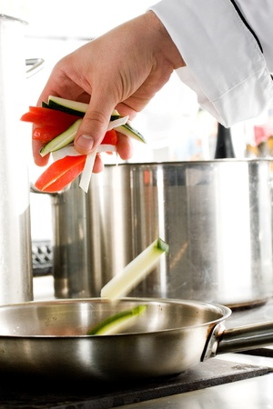 Chef hands add vegetables on a frying pan on professional kitchen photo