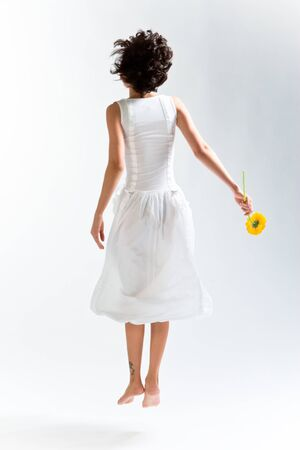 Young woman in with dress jumping up with flower