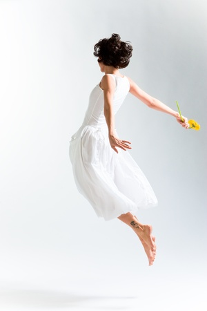Young woman in with dress flying with flower Stock Photo