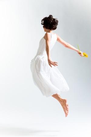 Junge Frau im Kleid mit Fliegen mit Blume
