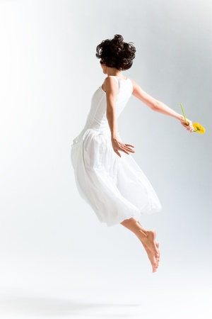 Young woman in with dress flying with flower Stock Photo - 10239091
