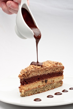 A piece of fresh baked delicious sponge-cake with chocolate sauce on a white plate. A hand pouring chocolate sauce out of a sauceboat on it. photo