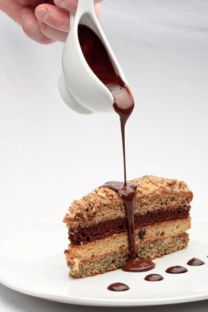 A piece of fresh baked delicious sponge-cake with chocolate sauce on a white plate. A hand pouring chocolate sauce out of a sauceboat on it.