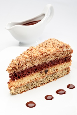coffeetime: A piece of fresh baked delicious sponge-cake with chocolate sauce on a white plate. A hand pouring chocolate sauce out of a sauceboat on it.