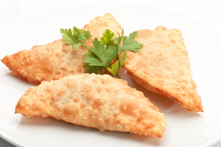 Asian cuisine- chebureki – pasties isolated on white background decorated with dill
