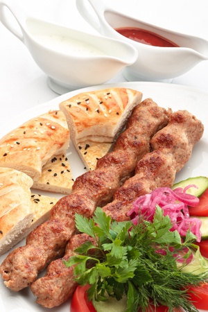 chicken kebab: Chicken kebab with a side salad and bread decorated on a white background