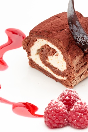 coffeetime: Chocolate roll with crud and mango cream decorated with raspberry and sauce on a white background