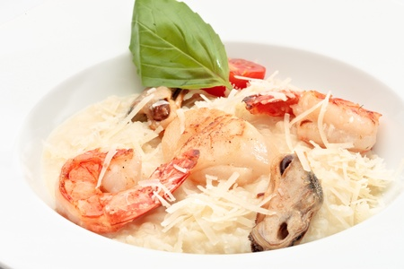 Close up of risotto with seafood in a white bowl on a white background Stock Photo