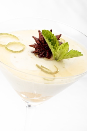 Close-up of lime and pear mousse decorated with anise and mint on a white background