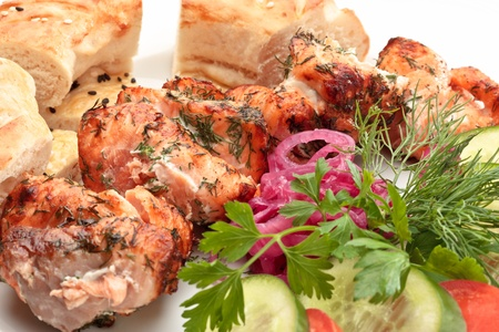 Close-up of salmon barbecue colorfully decorated with onion, parsley and dill
