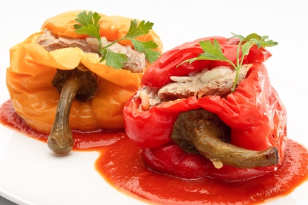 Colorful Bulgarian peppers stuffed with minced meat and rice on a white plate Stock Photo