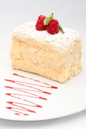coffeetime: mille-feuille with raspberry on top decorated on a white background Stock Photo