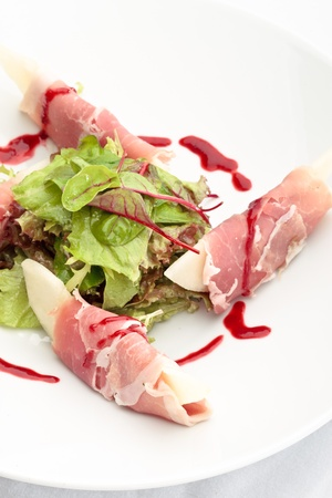Parma ham with melon decorated with lettuce on a white background
