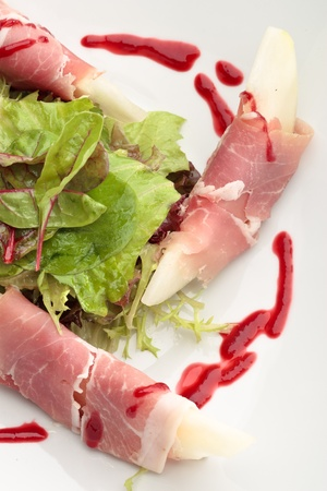 Parma ham with melon decorated with lettuce on a white background photo