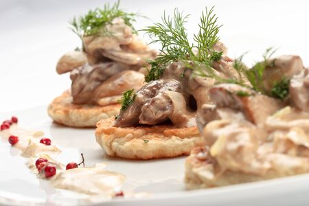 jewish cuisine: potato pancakes on plate with with mushrooms and dill