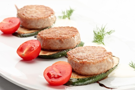 Russian chicken cutlets decorated with tomatoes and squash on a white background photo