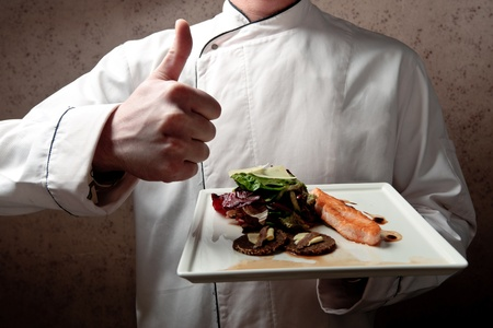 A chief dressed in white holding a white tray with roasted salmon fillet and vegetable salad elegantly decorated photo
