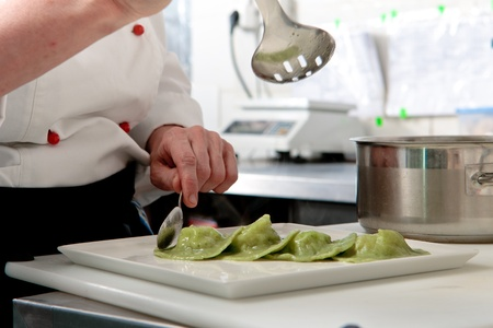 masterly: A chief cook masterly preparing delicious green ravioli with pesto sauce at the kitchen Stock Photo
