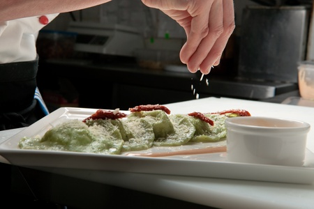 masterly: A chief cook masterly preparing delicious green ravioli with pesto sauce at the kitchen decorating raviolli with parmesan Stock Photo