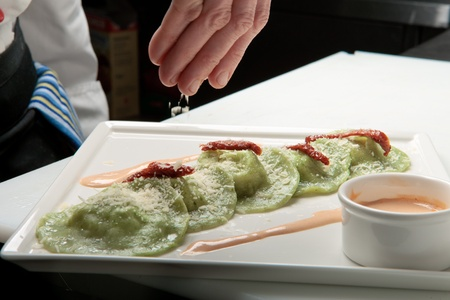 A chief cook masterly preparing delicious green ravioli with pesto sauce at the kitchen decorating raviolli with parmesan Stock Photo