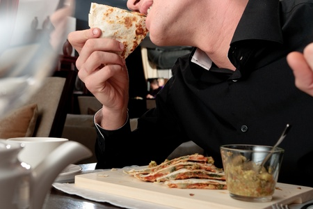A handsome young man eating delicious arabian pita with rice and vegetable stuffing at a table elegantly served