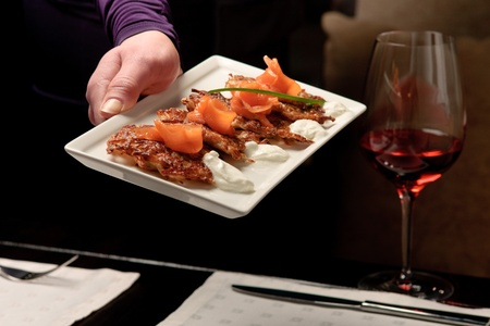A man�s hand holding a white tray with crispy potato pancakes decorated with salmon and sour cream photo