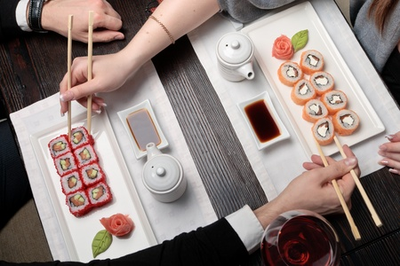 chopstick: Japanese food, a man and a woman eating maki sushi roll with chopsticks at a table elegantly served Stock Photo