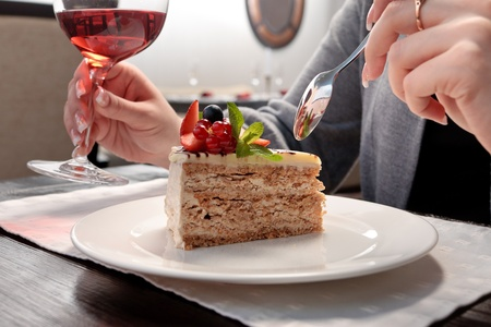 plato del buen comer: Un pedazo de la torta con frutas del bosque decorado con hojas de menta en un plato blanco en un restaurante, una mujer sentada, sosteniendo una copa de vino