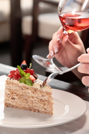 A piece of cake with forest berries decorated with mint leaf on a white plate in a restaurant, a woman sitting, holding a glass of wine