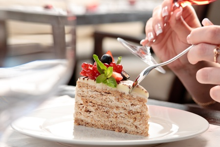 trozo de pastel: Un pedazo de la torta con frutas del bosque decorado con hojas de menta en un plato blanco en un restaurante, una mujer sentada, sosteniendo una copa de vino