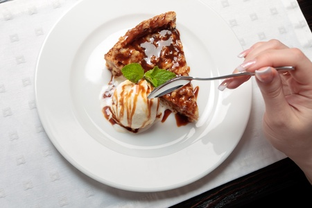 A piece of caramel cake with a scoop of ice-cream decorated with mint leaf on a white plate in a restaurant