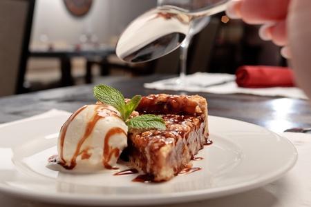 plato del buen comer: Un pedazo de pastel de caramelo con una cucharada de helado decorado con hojas de menta en un plato blanco en un restaurante