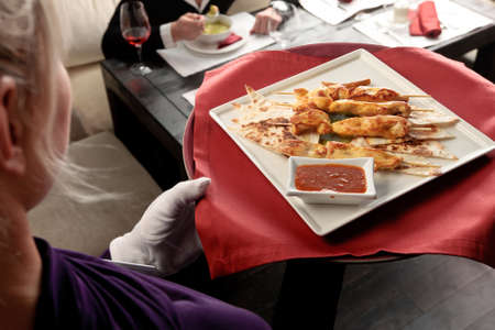 An attractive blond waitress serving grilled chicken elegantly decorated, on a red tray Stock Photo