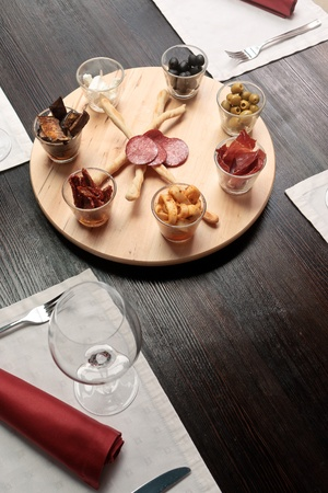 A wooden tray with delicious, spicy set of snacks on a table elegantly served photo