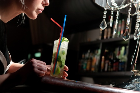 mohito: A young beautiful girl drinking cool mohito with a straw in a cafe