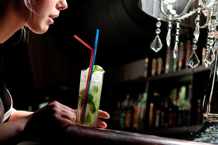 A young beautiful girl drinking cool mohito with a straw in a cafe Stock Photo - 11123542