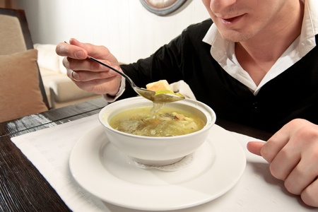mealtime: A young man eating fish soup, sitting at a table elegantly served in a restaurant, close up Stock Photo