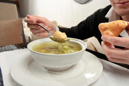cooked fish: A young man eating fish soup, sitting at a table elegantly served in a restaurant, close up Stock Photo
