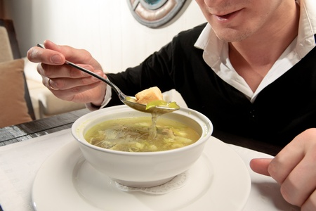 A young man eating fish soup, sitting at a table elegantly served in a restaurant, close up photo